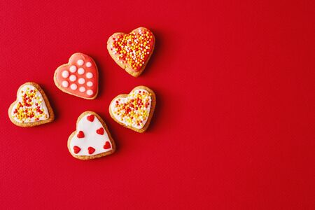 Decorated with icing and glazed heart shape cookies on red background with copy space. Valentines Day food concept Stock Photo - 137486252