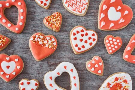 Background of decorated with icing and glazed heart shape cookies on gray background, flat lay. Valentines Day food concept Stock Photo - 137486561