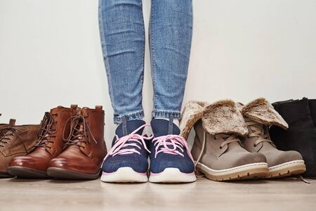 Woman chooses comfortable brown leather shoes among bunch of different pairs