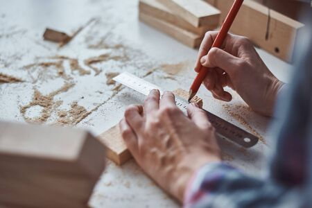 Carpenter hands taking measurement with pencil of wooden plank. Concept of DIY woodwork and furniture making Stock Photo