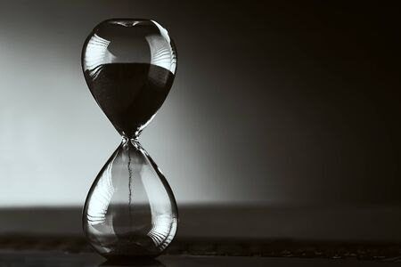 Hourglass on dark background with copy space. Concept of running out of time and deadline Reklamní fotografie
