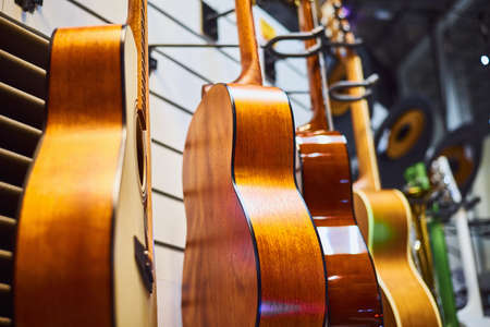 Row of classic acoustic guitars in the store