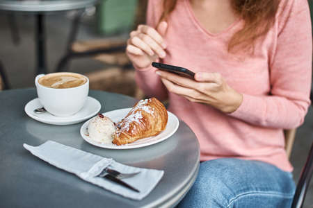 Woman have breakfast in caffe and using smartphone. Girl chatting and using internet with phone during coffee break with croissant