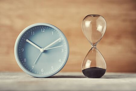 Hourglass and alarm clock on desk, close up