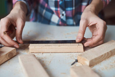 Carpenter hands taking measurement with pencil of wooden plank. Concept of DIY woodwork and furniture making Imagens