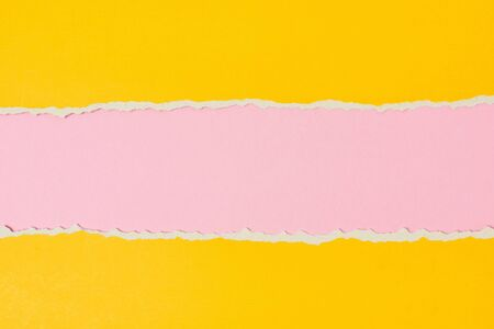 Torn ripped paper edge with copy space, pink and yellow color background Фото со стока