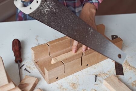 Process of carpenter hands sawing wooden board. Concept of DIY woodwork and furniture making