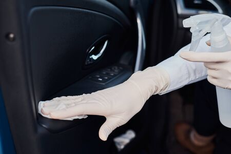 Woman cleaning car with disinfection spray to protect from coronavirus Stock Photo