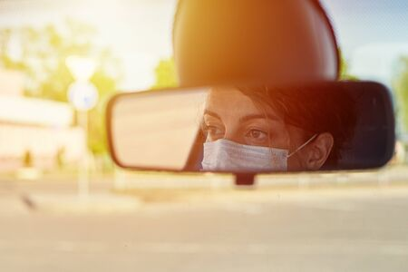 reflection of woman in protective medical mask in the rear view mirror in car. Virus protection and healt care concept