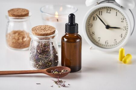 Herbal medicine for treat depression and insomnia concept. Alarm clock, medicine herbs and aromatherapy oil on white background