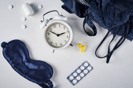 Insomnia and sleeping trouble concept. Alarm clock, sleeping mask, ear plugs and pills on white background, top view