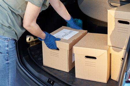 Donation and volunteering concept. Woman in gloves load box in car trunk.