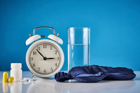 Insomnia problem and sleeping trouble concept. Alarm clock, glass of water, ear plugs and pills on blue background