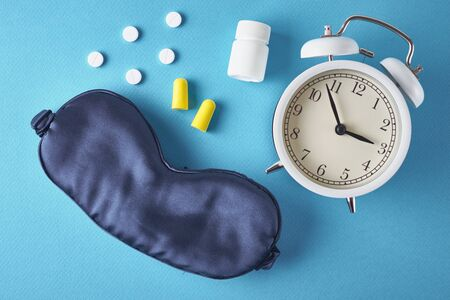 Insomnia problem concept. Alarm clock, sleeping mask, ear plugs and pills on blue background, top view