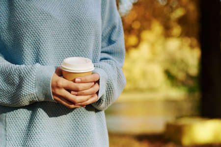 woman hold cup of coffe takeaway in autumn park