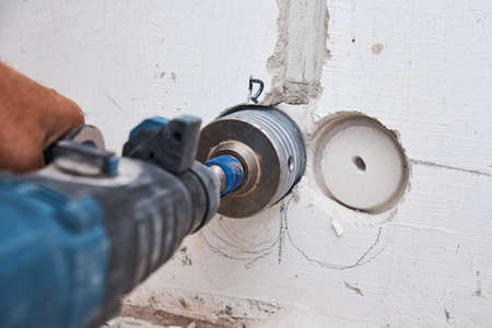 Builder with hummer drill perforator drills hole in the wall