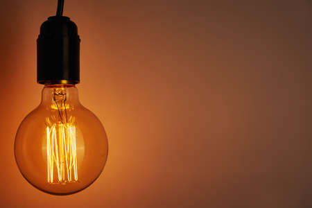Vintage light bulb on orange background with copy space. Glowing edison bulb