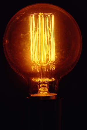 Vintage light bulb on black background, close up Glowing edison bulb
