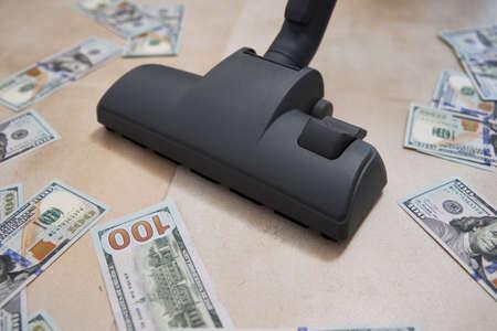Vacuum cleaner sucks usd dollar banknotes. Launder money concept 免版税图像