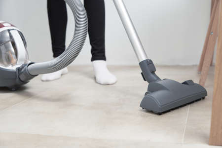 Woman using vacuum cleaner at the floor