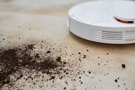 Robot vacuum cleaner cleans dirt on the floor. Smart home concept
