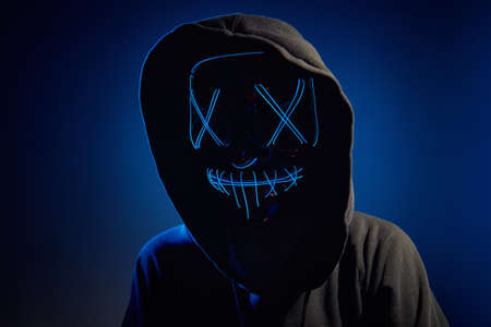 Anonymous man in a hood hiding face behind neon glow scary mask on dark background. Horror concept
