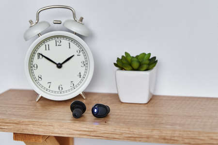 Wireless earphones on the shelf with alarm clock and house plant. Headphones in home office interior