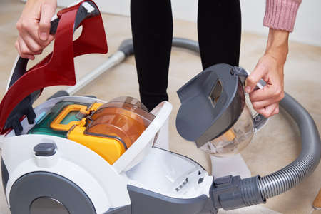 woman takes out container of dust from vacuum cleaner