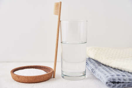 Bamboo toothbrush, baking soda and glass of water on a white background. Eco friendly toothbrushes, zero waste concept