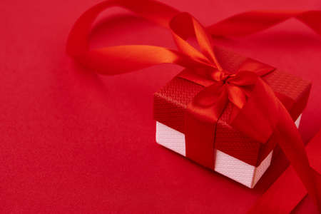 Valentine's Day background. Gift box with festive ribbon on red background. Valentine day concept. Top view, flat lay