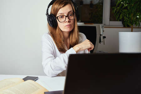 Remote work. Online courses, distance education and e-learning concept. Woman in headphones listen audio course at laptop and makes notes in notebook