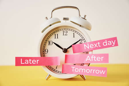 Procrastination, delay and postpone concept. Alarm clock with sticky notes   later, tomorrow, next day and after on the yellow background