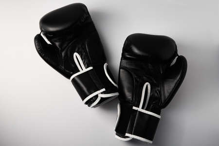 Pair of black boxing gloves on white background, close up