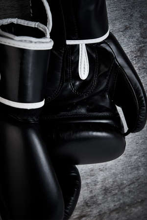Pair of black boxing gloves on dark background, close up