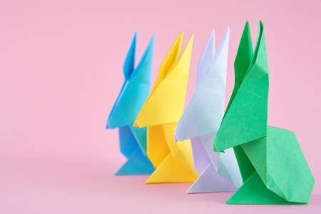 Paper colorful origami Esater rabbits on pink background. Easter celebration concept