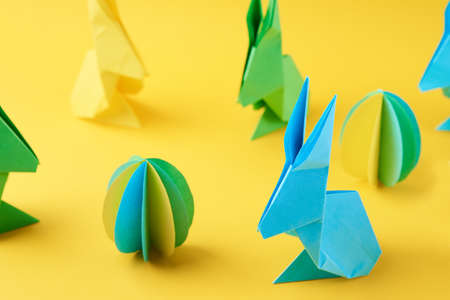 Paper origami Esater rabbits and colored eggs on yellow background, top view. Easter celebration concept