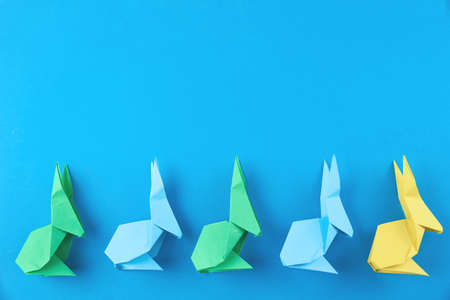 Paper colorful origami Esater rabbits on blue background, top view. Easter celebration concept