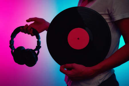 Woman holds retro vinyl disc and headphones with neon light