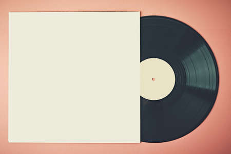 Old retro vinyl disc in paper case on pink background, mock up. Vintage toned photo