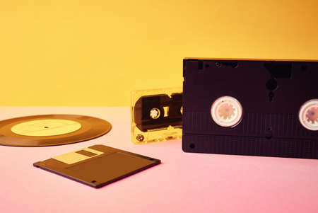 Vinyl disc, floppy diskette, vhs and tape cassete on yellow background. Vintage, retro and nostalgia concept
