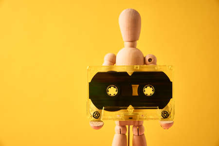 Wooden man holds retro cassette tape on yellow background, copy space Zdjęcie Seryjne