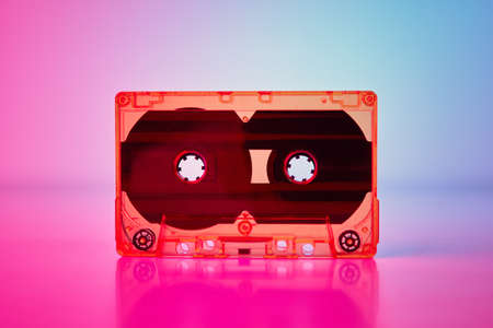 Retro cassette tape on colorful neon background, front view