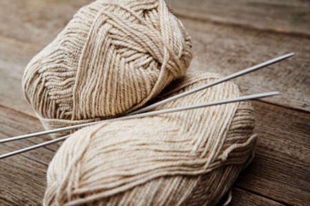 Two skeins of woolen yarn and needles for knitting on wooden background