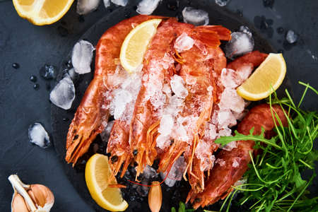 Fresh shrimps with lemon on dark background. Red raw prawns.Frozen seafood