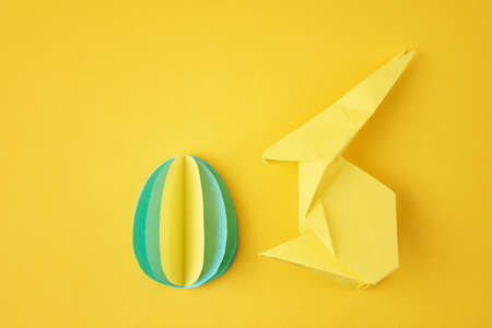 Paper origami Esater rabbit and colored egg on yellow background. Easter celebration concept Zdjęcie Seryjne