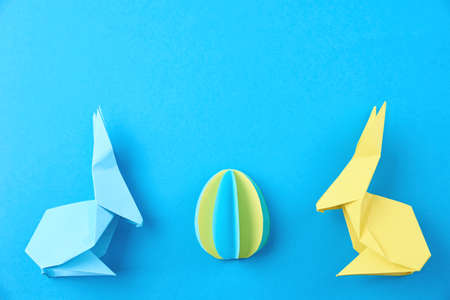 Two paper origami Esater rabbits and colored egg on blue background. Easter celebration concept