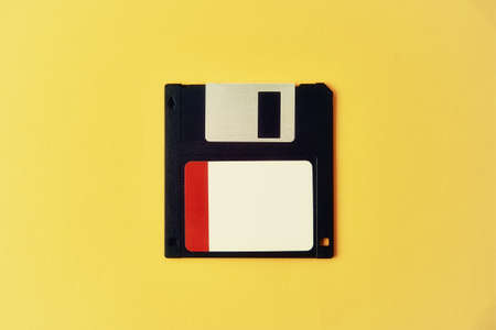 Black floppy diskette on yellow background. Vintage computer diskette, close up
