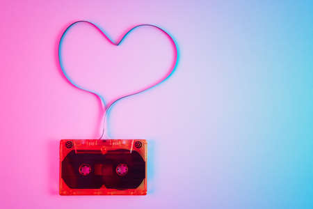 Retro cassette on colorful neon background with magnetic tape in shape of heart. Love music concept