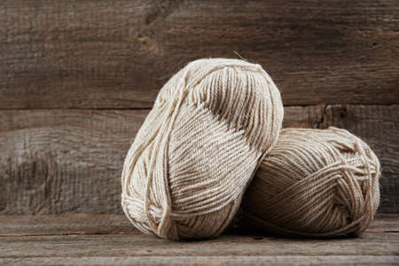 Two skeins of woolen yarn and needles for knitting on a wooden background