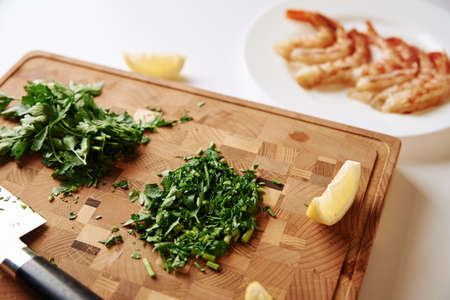 Cooking dinner. Chopped parsley on a cutting board and fresh shrimp on the table Zdjęcie Seryjne